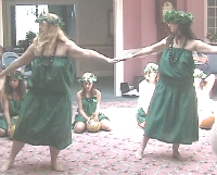 "Bev ""Peweli"" and student dance in green dresses"